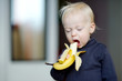 Toddler girl eating a banana