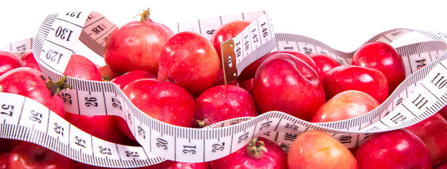 healthy food. Delicious apples with measuring tape on a white