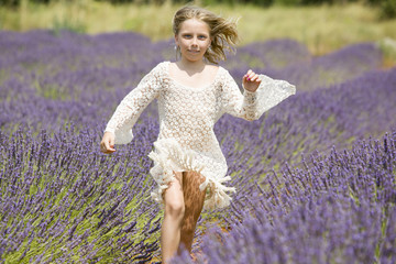 Young girl runs in purple lavender field