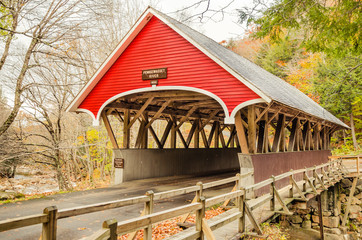 Red Wooden Covered Bridge in Autumn and Cloudy Sky
