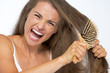 Angry woman having hard time combing hair