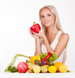 Beautiful young woman holding pepper behind a table full of frui