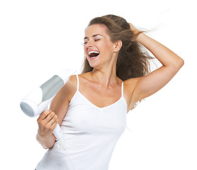 Smiling young woman singing while blow-dry