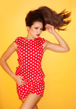 Hot woman wearing red polka dots dress with black stiletto