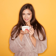 Seductive woman wearing bathrobe and drinking hot coffee