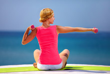 Jonge vrouw doet oefeningen met de hand gewichten op het strand