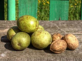 Mature and green walnuts on table