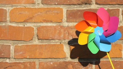 One colorful pinwheel over old brickwall background, 1080