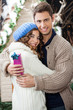 Couple With Gift Box Embracing At Christmas Store