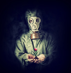 Man in gas mask holding flower in palms