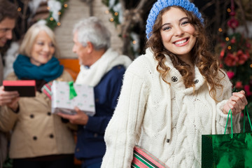 Happy Woman With Family In Christmas Store