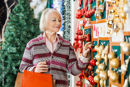 Woman Selecting Christmas Ornaments At Store