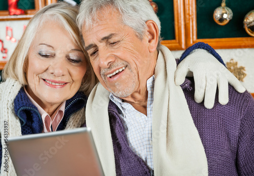 Couple Using Digital Tablet At Christmas Store