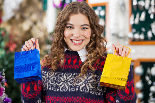 Happy Woman Holding Small Shopping Bags In Store