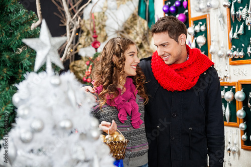 Couple With Bauble Basket In Christmas Store