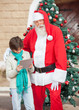 Santa Claus Standing With Boy Using Digital Tablet