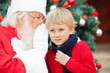 Santa Claus Whispering In Boy's Ear