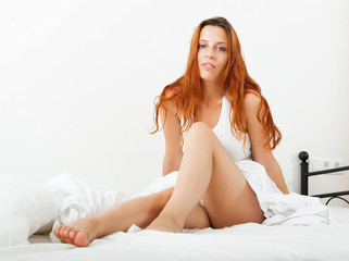 woman lying on white sheets on the bed at home