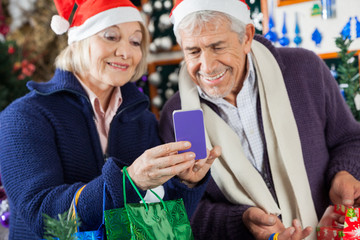 Senior Couple Using Mobilephone At Christmas Store