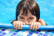 little girl with beautiful eyes peeking out of the pool