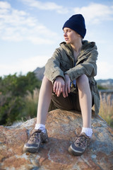 Woman wearing cap sitting on a rock