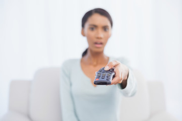 Shocked woman sitting on sofa changing tv channel