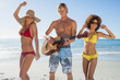 Three friends having fun on the beach and playing guitar