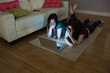 Two surprised friends lying on floor using laptop together in th