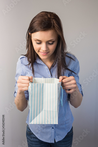 Smiling pretty brunette receiving a present
