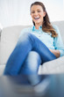 Attractive cheerful woman sitting on sofa
