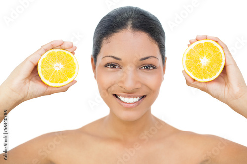 Smiling black haired model holding orange slices