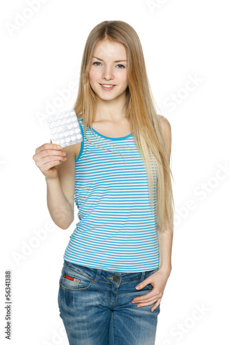 Young woman with pills over white