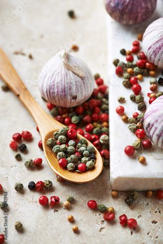Assorted peppercorns, coriander seeds and garlic bulbs