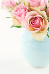 Roses in a light blue vase on cream beige shabby chic background