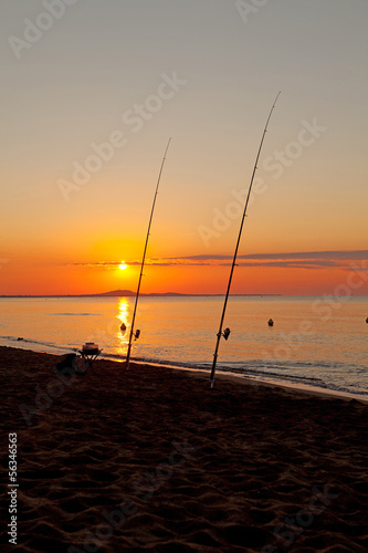 Fishing rod at sea by sunset