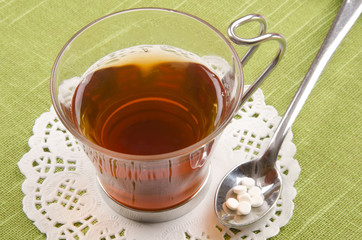 black tea in a glass cup with sweetener