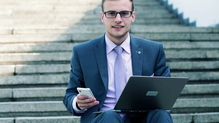 Happy businessman with smartphone and laptop on stairs