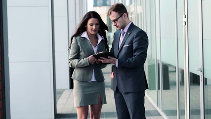Businessman and businesswoman working with tablet outdoors