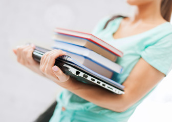 student with books, computer and folders