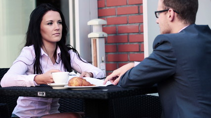 Businesswoman and businessman talking in cafe
