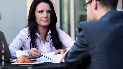Businesswoman and businessman talking over contract in cafe