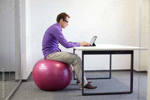 bad sitting posture at desk on stability ball with tablet