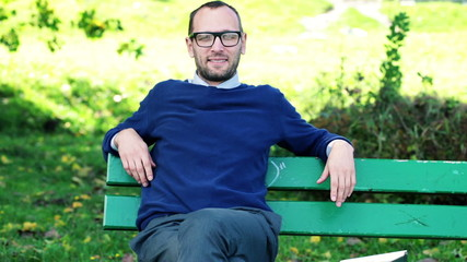 Happy young businessman relaxing on bench in park