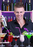 Portrait of handsome barman with different cocktails cocktail,