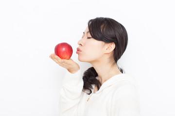 リンゴにキスする女性