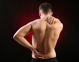 Young man with back pain, on red background