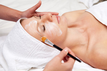 Spa therapy for woman receiving facial mask at beauty salon