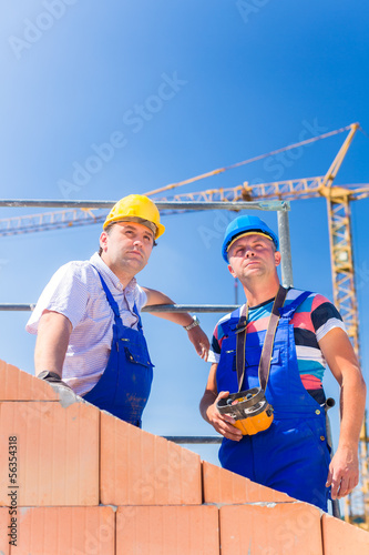 Construction site workers building house with crane