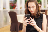Image of young businesswoman looking at her smartphone in cafe