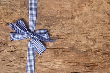 Weiß Blau karierte Schleife auf rustikalem Holzbrett